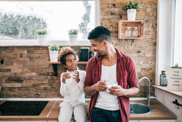 台所で彼の小さな娘とミルクのガラスを持っている魅力的な若い男。
