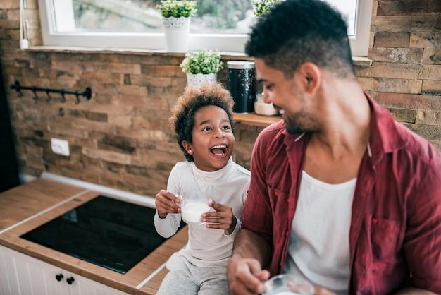 Счастливый афро-американский мужчина и его дочь, пить молоко по утрам.
