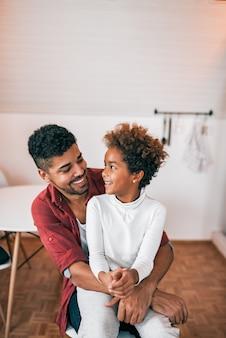 アフリカ系アメリカ人の父と娘を自宅で一緒に笑っています。