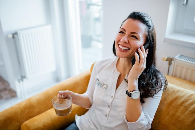 陽気な若い女性が自宅でコーヒーカップを保持している、携帯電話で話しています。
