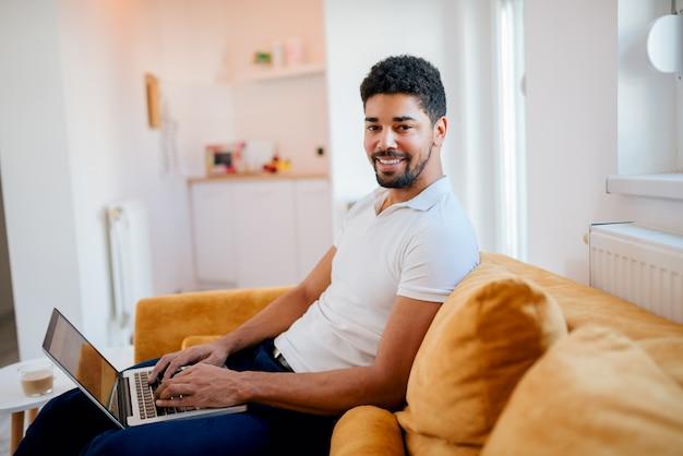 カメラを見て、自宅でラップトップに取り組んで笑顔のフリーランサー。