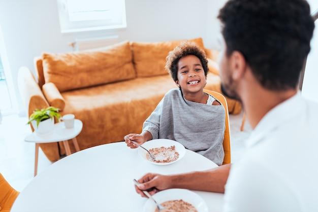 Маленькая девочка ест хлопья на завтрак с отцом.