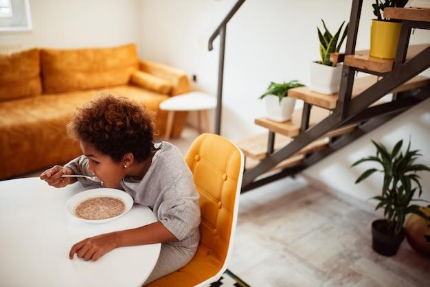 朝食に穀物を食べる少女。