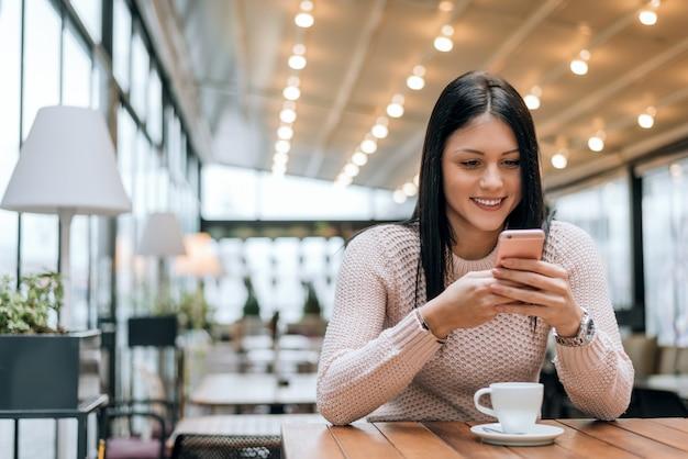 Молодая женщина в современном кафе, чтение текстового сообщения со своего мобильного телефона.