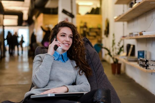 モダンな環境で電話で話している美しい白人女性。