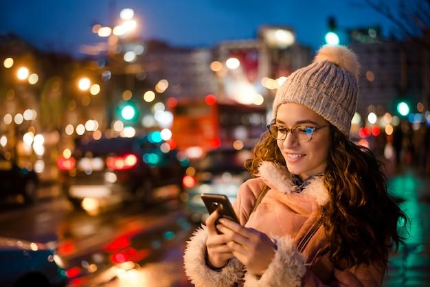 都市道路の近くの夜に彼女の携帯電話を使用して美しい若い女性の屋外のポートレート。