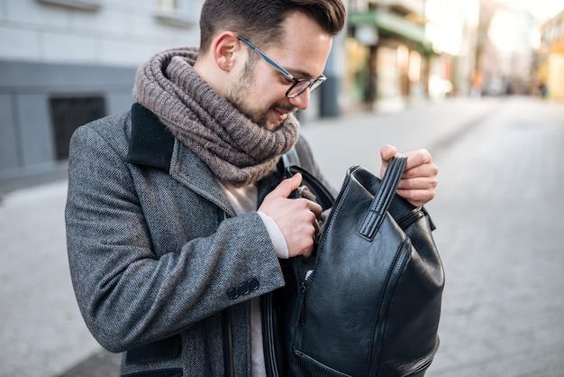 街でバックパックを探している若い男のクローズアップ画像。