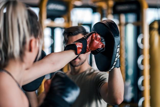 彼女のスパーリングパートナーの手袋を打つ女性ボクサー、クローズアップ。
