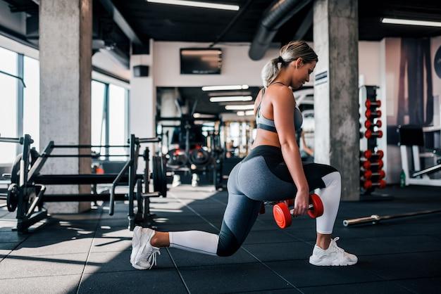 ジムで突進をしている若い筋肉女性の側面図です。