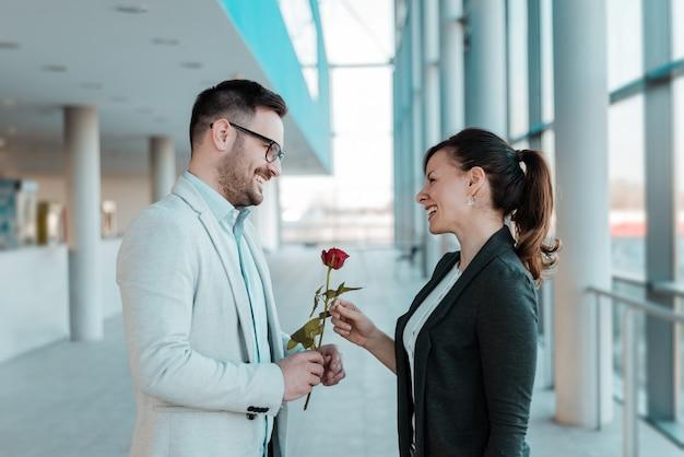 彼のかわいい同僚にバラをあげるビジネスマン。