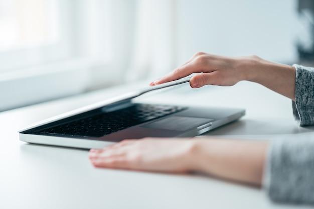 女性の手のクローズアップイメージは白いテーブルにラップトップを開閉します。
