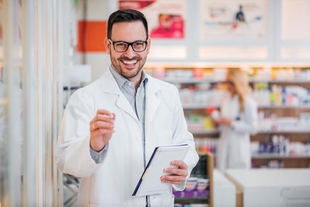 カメラに笑顔、クリップボードとハンサムな薬剤師の肖像画。