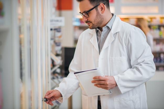 Аптекарь держа рецепт и проверяя для медицины в магазине фармации.