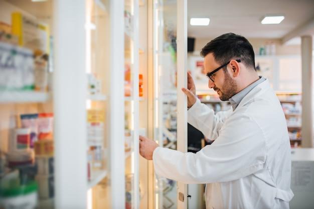 Аптекарь проверяя для медицины в полке на аптеке.