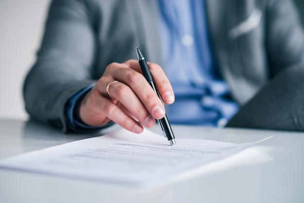 契約上のペンを持っているビジネスエグゼクティブの手、白いテーブルの上のドキュメントクローズアップ。