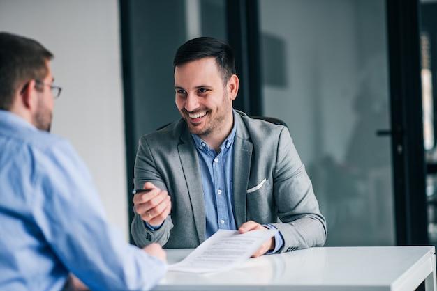 契約に署名するためのクライアントにペンを与える実業家の笑みを浮かべてください。