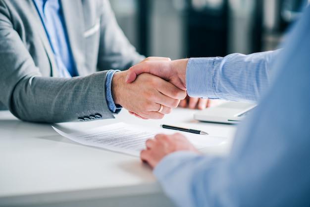 Бизнесмены рукопожатие за подписанный контракт.