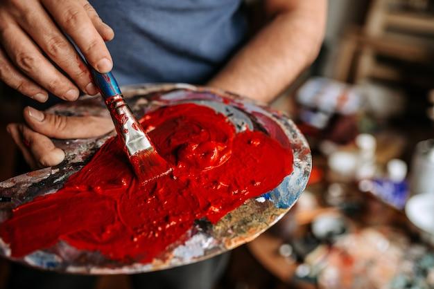 Палитра художника покрыта красной краской.