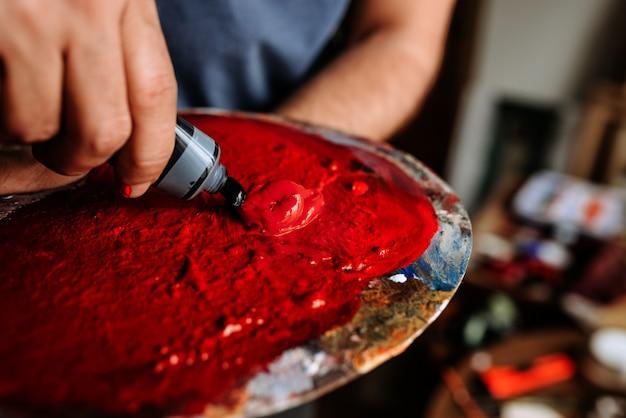 アーティストはパレットのチューブから赤いペンキを絞ります。