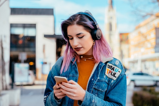 Портрет фиолетовой с волосами девушки используя телефон и слушая музыку на наушниках.