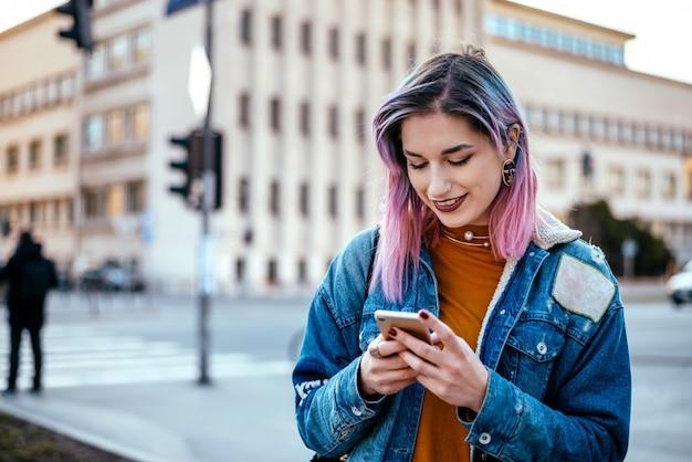街で携帯電話を使用してライラックの髪型と都市の女の子。