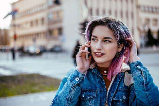 屋外の電話で話している染めの髪を持つ若い女性。