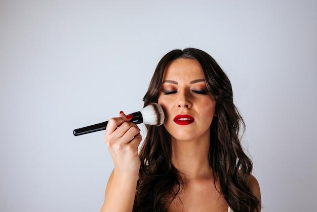 目を閉じて化粧品のブラシで赤面を適用する女性の肖像画。