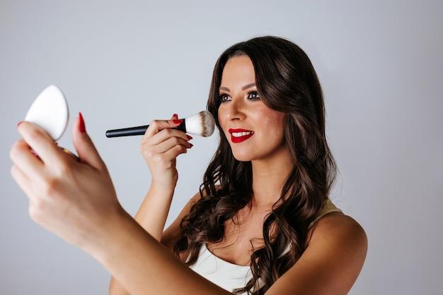 鏡を押しながらブラシを使用して彼女の顔にメイクアップを適用する女の子