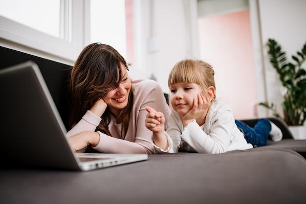 彼女の母親と漫画を見ながらノートパソコンの画面を指しているかわいい女の子。