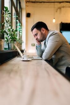 カフェでラップトップに取り組んでいる欲求不満の若手実業家のイメージ。