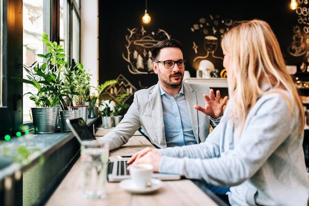 ハンサムな男がカフェで若いブロンドの女性に話しています。