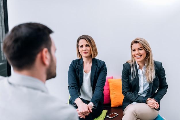 ビジネスの男性が休憩中に女性の同僚に話しています。