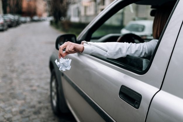女性開き手左右車の窓からゴミを投げます。
