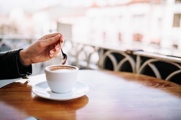 Женская рука держит ложку возле чашки кофе на открытом воздухе.