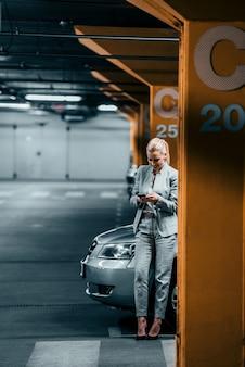 エレガントな女性は彼女の車のそばに立っているとスマートフォンを使用しています。