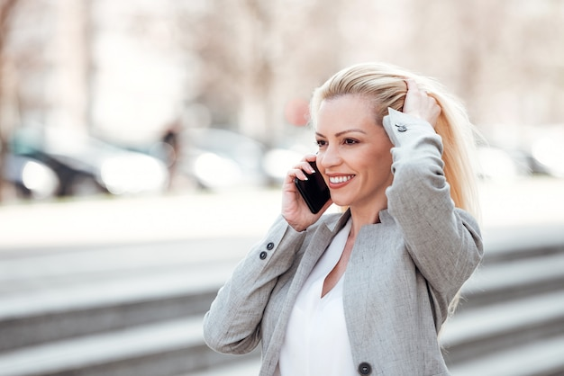 実業家、街を歩いて、電話で話して、彼女の髪に触れます。