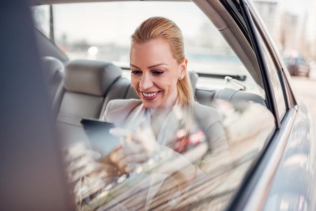 Успешная коммерсантка отправляя смс на умном телефоне пока сидящ на заднем сиденье в автомобиле.