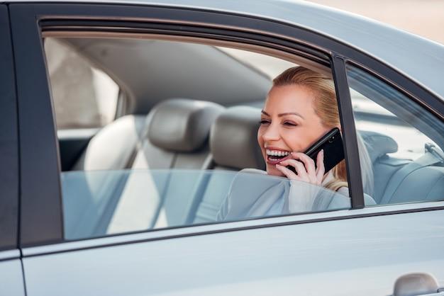 車の後部座席に座って携帯電話で話している笑顔のビジネス女性。