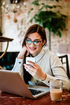 スマートフォンとラップトップを使用して眼鏡を持つ女性の笑みを浮かべてください。