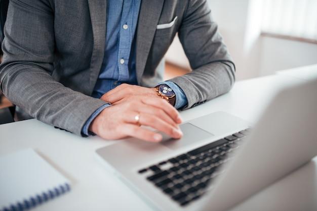 ビジネスの成功と技術の概念ラップトップに取り組んでフォーマルな服装のビジネスマンクローズアップ。
