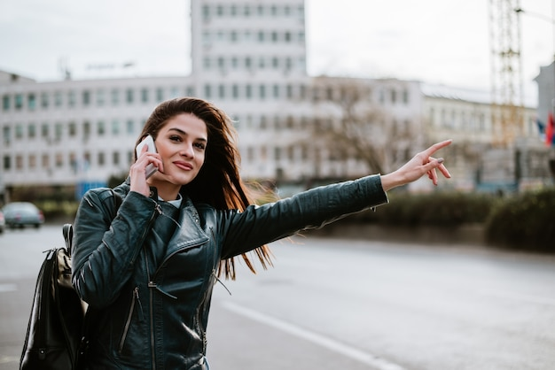 Великолепная женщина разговаривает по городской улице, ловит такси.