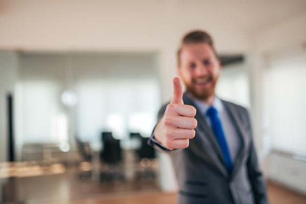 Молодой предприниматель в современный офисный интерьер, показывая большие пальцы руки вверх, фокус на переднем плане.