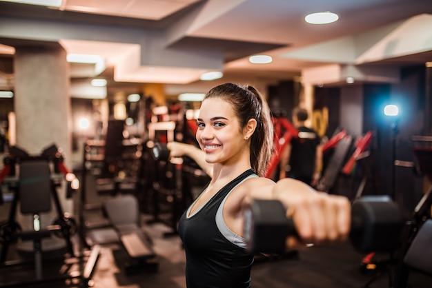 Улыбается спортивная женщина делает упражнения для оружия. тренируюсь с гантелями в тренажерном зале.