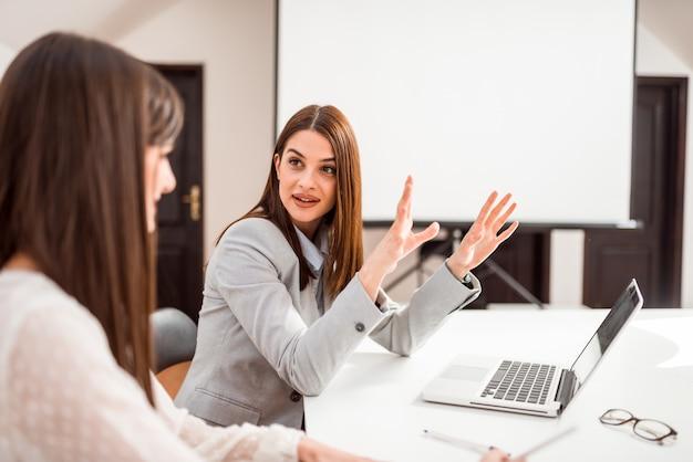 エレガントな女性実業家が彼女の従業員または会議室でクライアントに話しています。