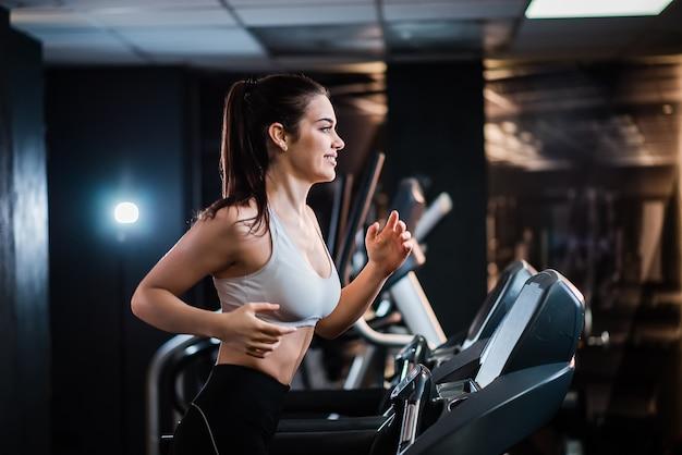 Молодой спортивный женщина с хвостиком, тренируясь в тренажерном зале, бег на беговой дорожке, вид сбоку.