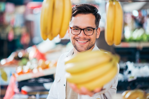 Молодой человек держа пук бананов на рынке фермера, конца-вверх.