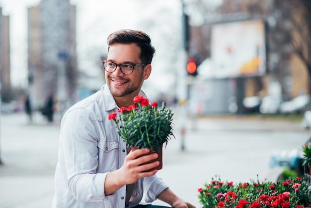 屋外の花を買う肯定的な若い男。
