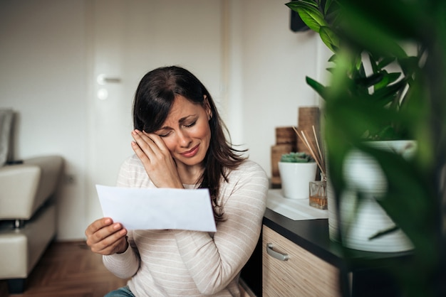Портрет печальной женщины сломаны после прочтения плохих новостей в письме у себя дома.