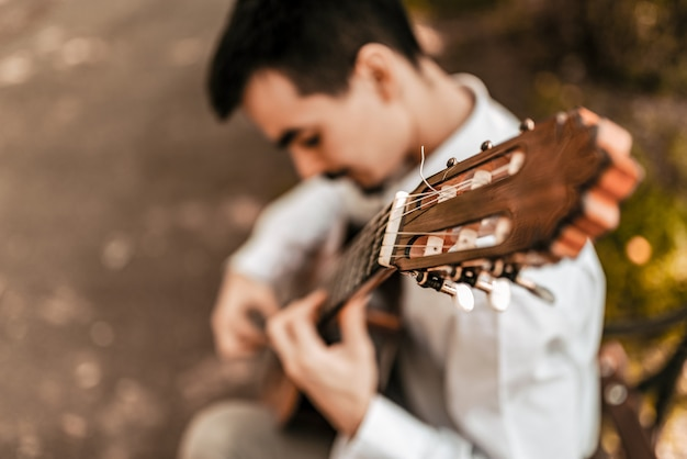 屋外のアコースティックギターを弾く男性ミュージシャンのイメージがぼやけています。ハイアングル。
