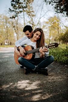 野外で遊ぶ彼のガールフレンドのギターを教える若い男。